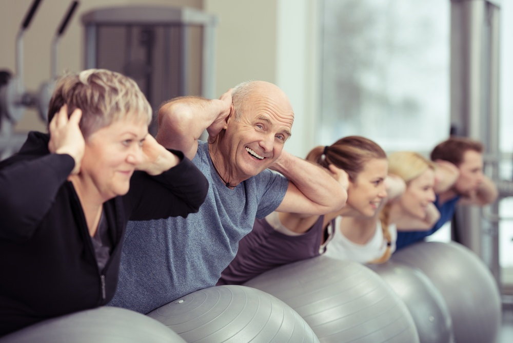 Elderly couple doing pilates class at the gym with a group of diverse younger people balancing on the gym ball with raised arms to tone their muscles in an active retirement concept.jpeg