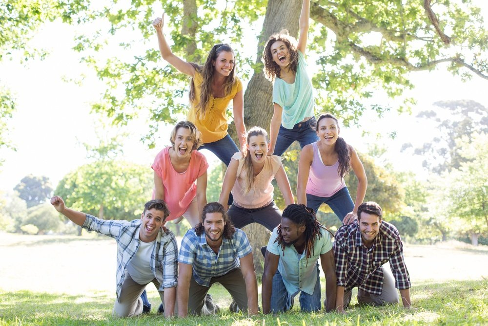Happy friends in the park making human pyramid on a sunny day.jpeg