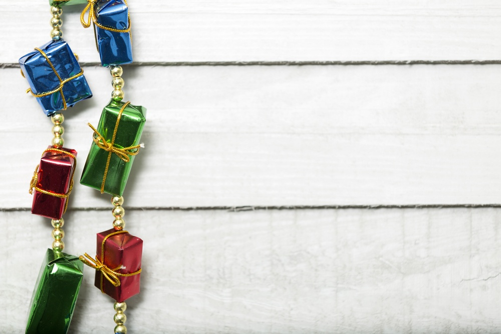 Bright christmas decoration of wrapped parcels against a light wooden wall.jpeg
