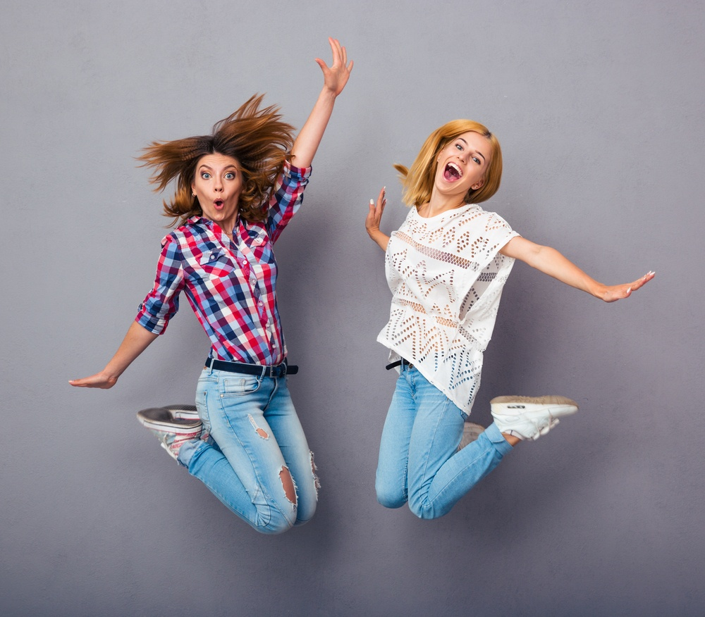 Two cheerful girls jumping over gray background.jpeg